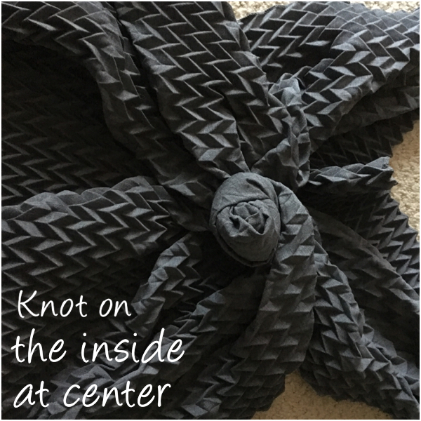 The center knot on the inside takes away the bulk on this scarf on Brenda Kinsel website